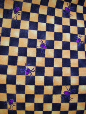 Close up of Hokus Pokus black orange gingham with purple spiders